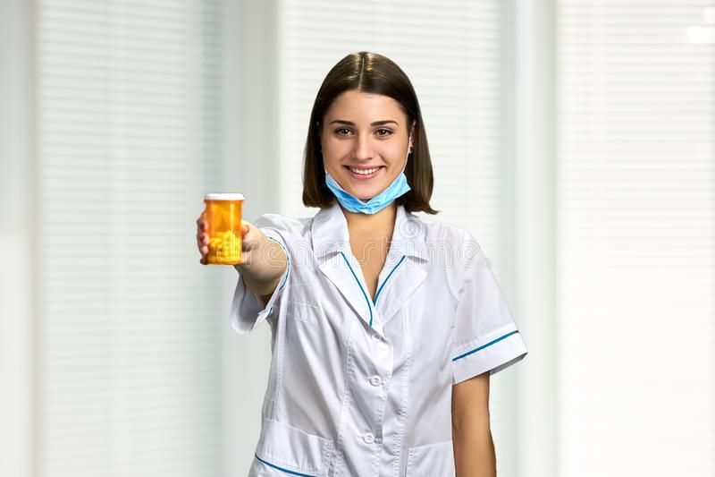 Junger lächelnder Doktor, der Pillen zeigt stockbild