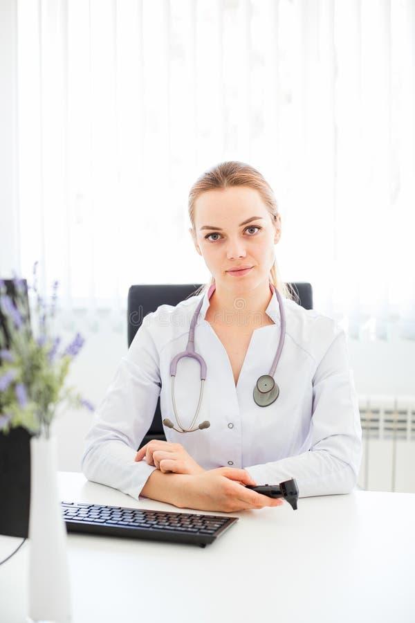 Junger lächelnder Doktor, der am Schreibtisch auf einem schwarzen Stuhl mit ihren Armen sitzt, kreuzte stockbilder