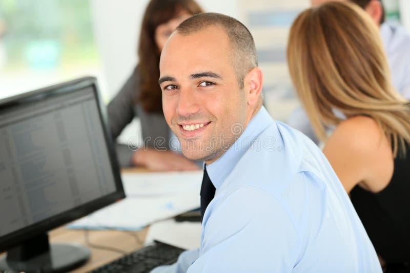 Junger lächelnder Geschäftsmann, der an Computer arbeitet lizenzfreie stockfotos