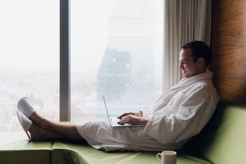 Junger lächelnder Geschäftsmann, der an Laptop-Computer dem tragenden weißen Bademantel sitzt nahe Fenster mit Tasse Kaffee arbei stockbild