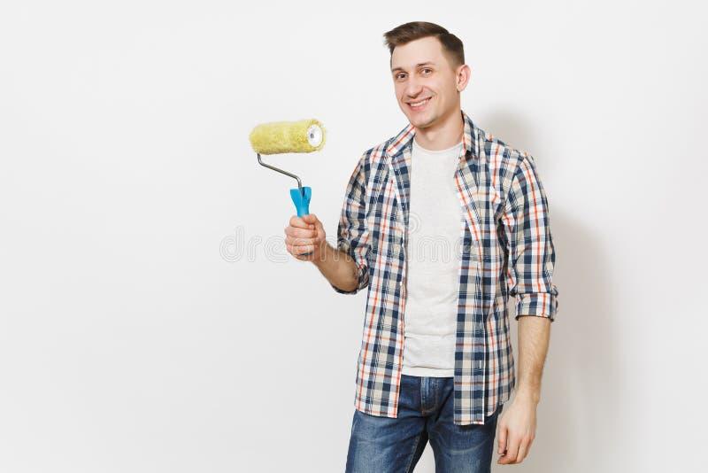 Junger lächelnder gut aussehender Mann in der zufälligen Kleidung, die Farbenrolle für das Wandbild lokalisiert auf weißem Hinter stockfotografie