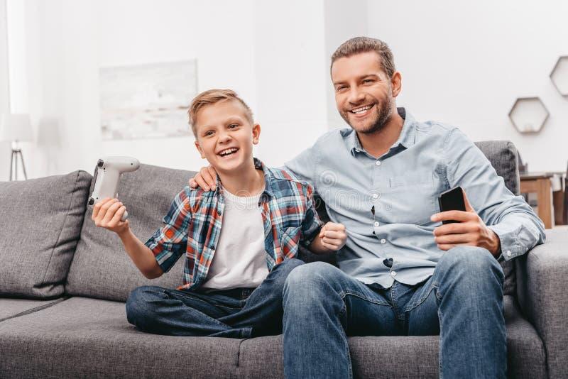 Junger lächelnder Junge, der gamepad hält und auf Couch sitzt lizenzfreie stockbilder
