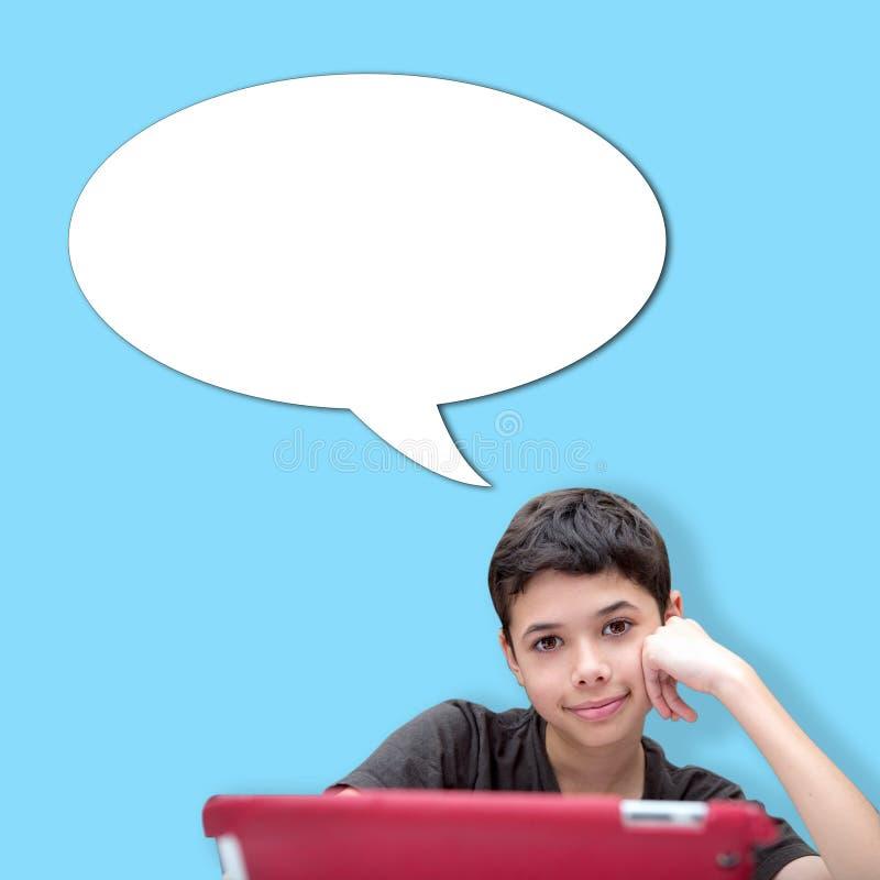 Junger lächelnder Junge mit einer Hand, die auf Backe mit Spracheblase gegen blauen Hintergrund stillsteht stockbilder
