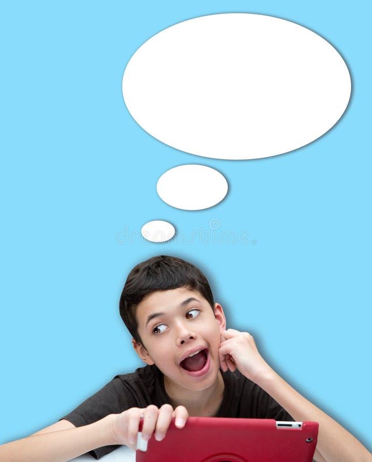 Junger lächelnder Junge mit einer Hand, die auf Backe mit Spracheblase gegen blauen Hintergrund stillsteht stockfotografie