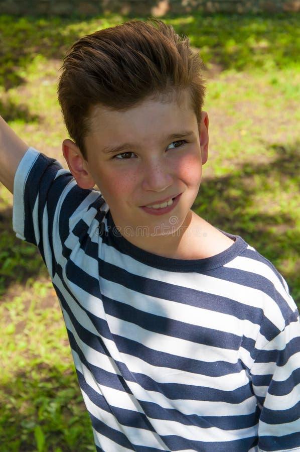Junger lächelnder Junge mit einer modernen Frisur auf dem Weg lizenzfreie stockbilder