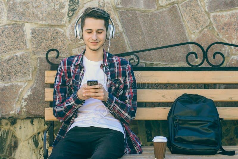 Junger lächelnder Kerl, der auf einer Bank sitzt und seinen Smartphone für das Hören Musik verwendet stockfotos