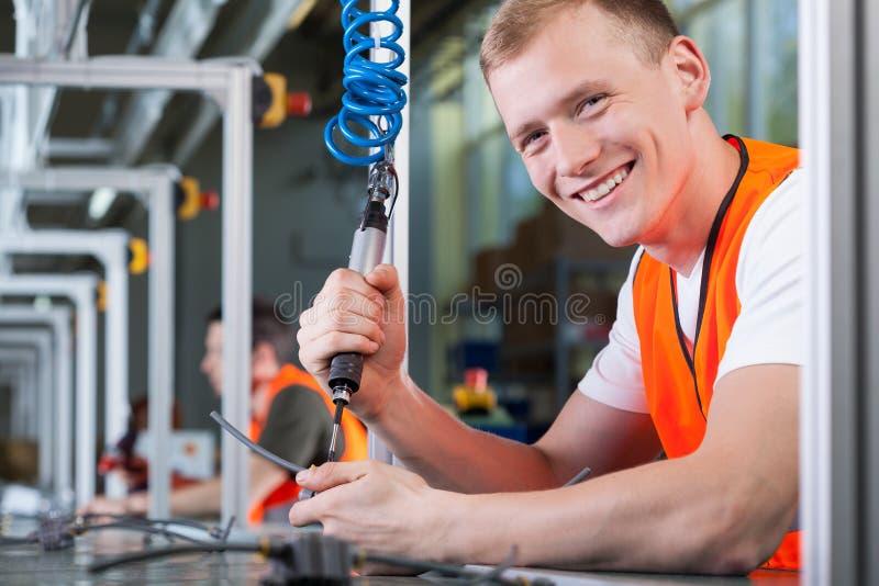 Junger lächelnder Mann, der an der Fertigungsstraße arbeitet lizenzfreies stockbild