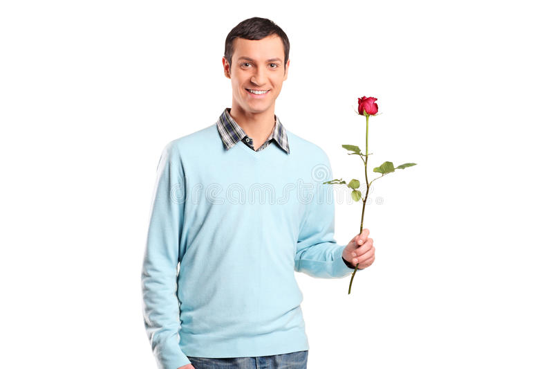 Junger lächelnder Mann, der eine Roseblume anhält stockfotos