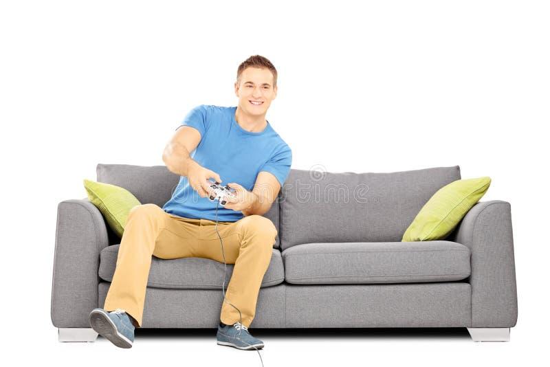 Junger lächelnder Mann gesetzt auf einem Sofa, das Videospiele spielt stockfotos