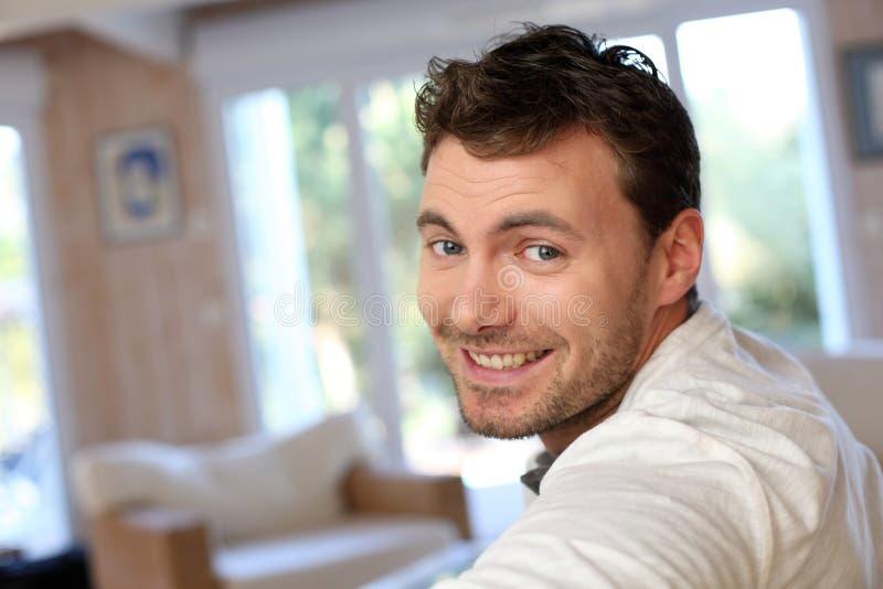 Junger lächelnder Mann im Wohnzimmer stockfotos