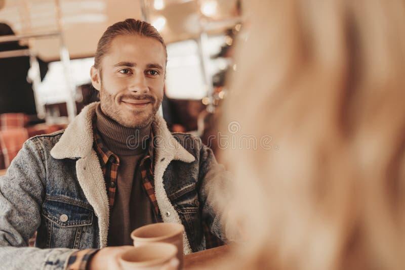 Junger l?chelnder Mann sitzen im Caf? mit geliebter Frau stockfoto
