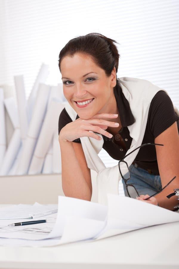 Junger lächelnder weiblicher Architekt mit Plänen lizenzfreie stockfotos