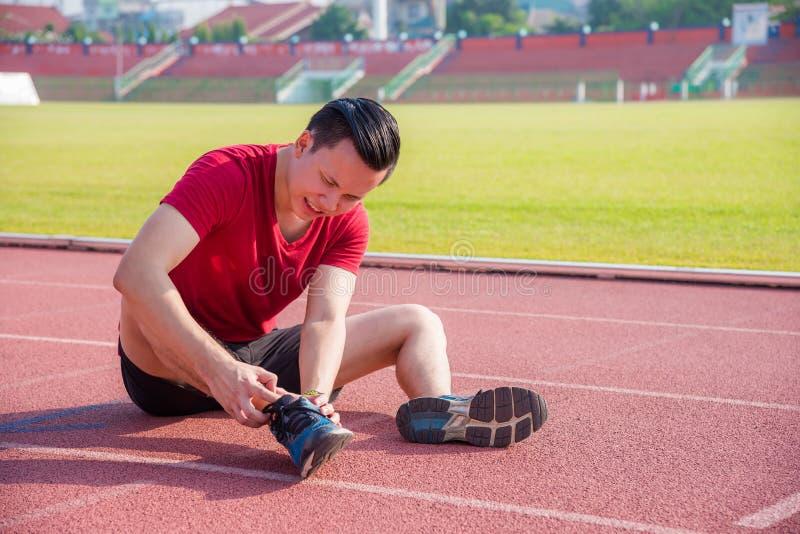 Junger Läufer, der die Schmerz am Gelenk zwischen dem Laufen hat stockbilder