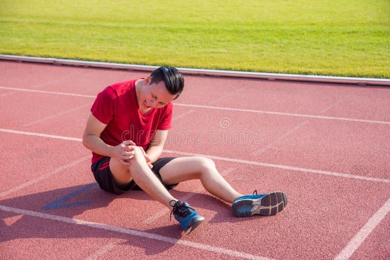 Junger Läufer, der die Schmerz am Knie zwischen dem Laufen hat stockfotos