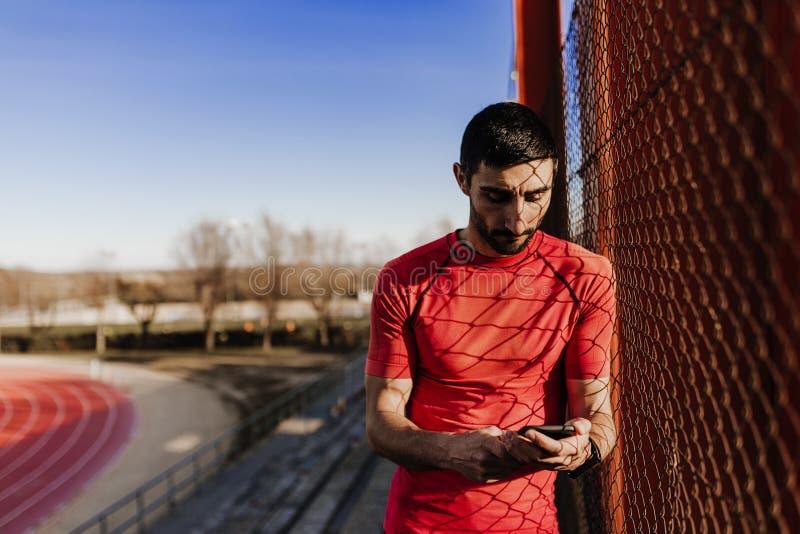 Junger Läufermann unter Verwendung des Handys bei Sonnenuntergang Sport draußen lizenzfreies stockfoto