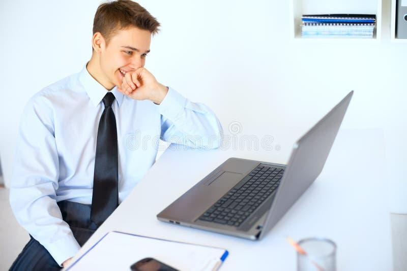 Junger lachender Geschäftsmann, der den Laptopschirm betrachtet lizenzfreies stockfoto