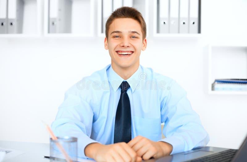 Junger lachender Geschäftsmann im Büro lizenzfreie stockfotografie