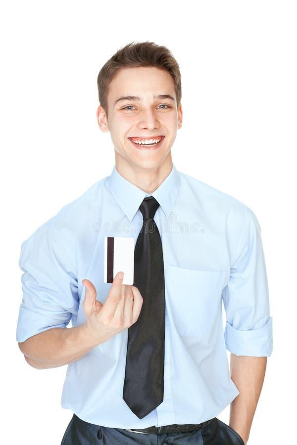 Junger lachender Mann, der eine Kreditkarte lokalisiert auf Weiß hält stockfotos