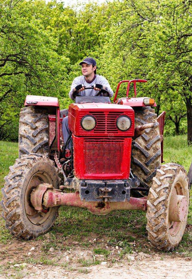 Junger Landwirt, der seinen Traktor fährt lizenzfreie stockfotos