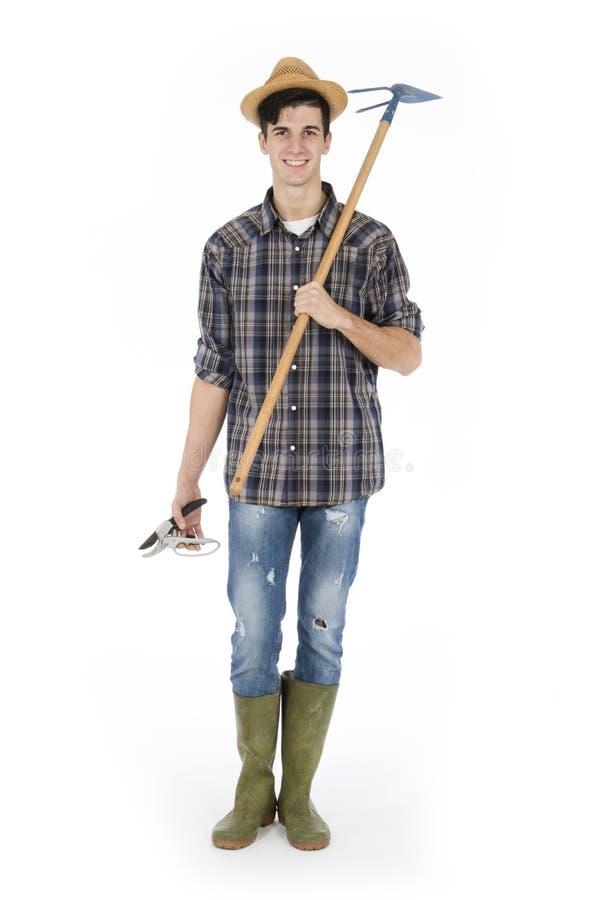 Junger Landwirt mit Arbeitswerkzeugen stockfoto