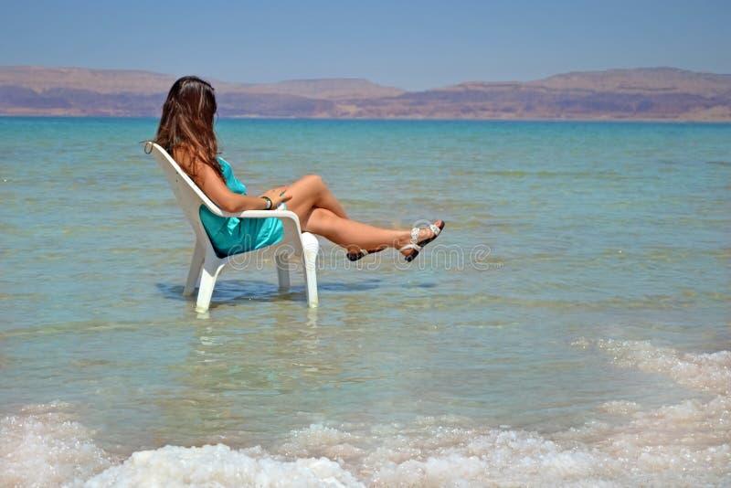 Junger langhaariger Brunette sitzt auf einem Stuhl in Israel Das Mädchen im Toten Meer betrachtet die Berge von Jordanien lizenzfreie stockfotografie