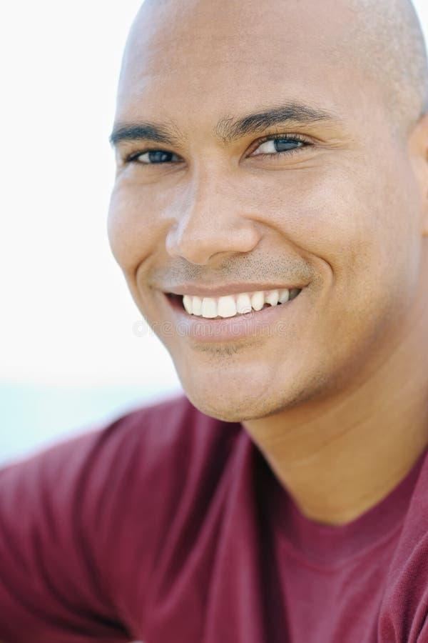 Junger Latinomann, der an der Kamera lächelt lizenzfreie stockfotos