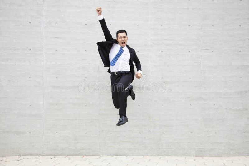 Junger laufender und springender Geschäftsmann stockbild