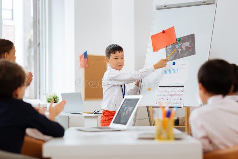 Junger Lehrer, der andere Kinder in einem Klassenzimmer unterrichtet stockbild