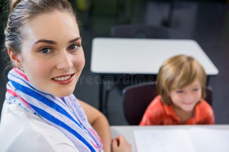Junger Lehrer mit Jungen im Klassenzimmer lizenzfreies stockbild