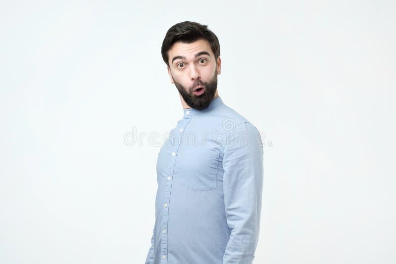 Junger lustiger hispanischer Mann mit schwarzem Bart ist entsetzt und überrascht stockbild
