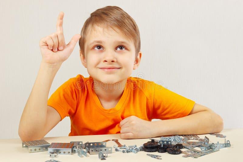 Junger lustiger Ingenieur denkt, das vom mechanischen Erbauer zusammenbauen stockfoto