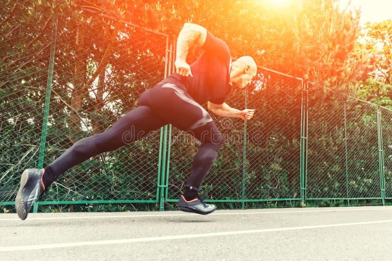 Junger männlicher Athlet, der weg von der Anfangslinie in einem Rennen startet Läufer, der auf Rennbahn im Stadion läuft stockbilder