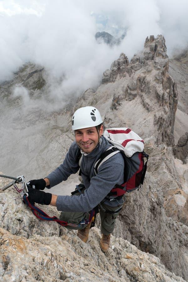 Junger männlicher Bergsteiger auf einem steilen und herausgestellten Felsengesicht, das a über Ferrata klettert lizenzfreie stockbilder
