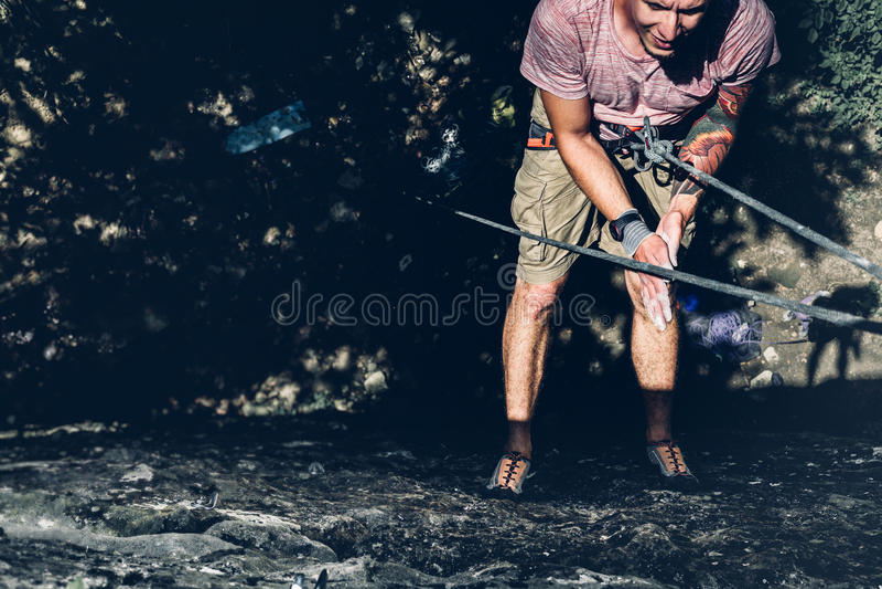 Junger männlicher Bergsteiger, der irgendwo an einem Felsen auf einem Seil und Blicken an der Wand hängt Extremes Lebensstil-Täti stockbild