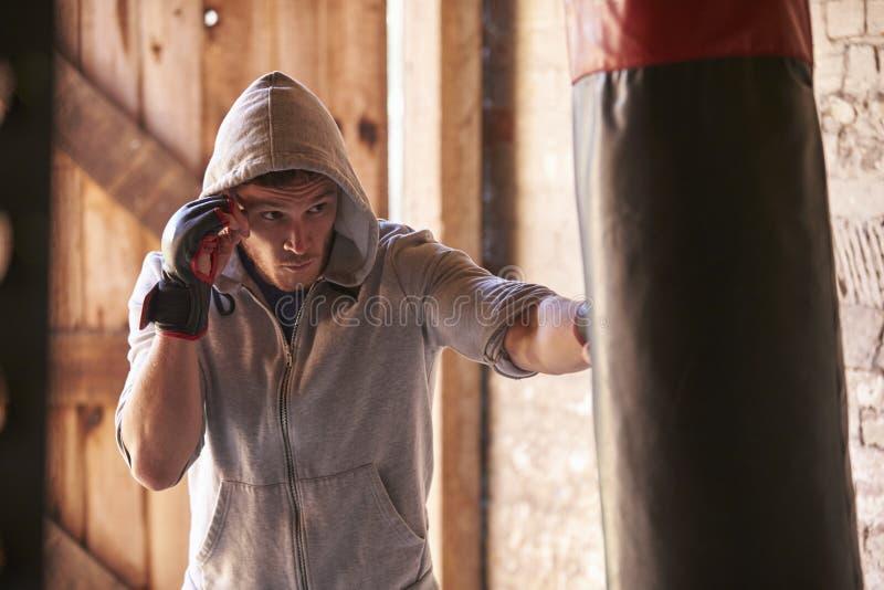 Junger männlicher Boxer, der mit Punchbag in der Turnhalle ausarbeitet lizenzfreie stockbilder