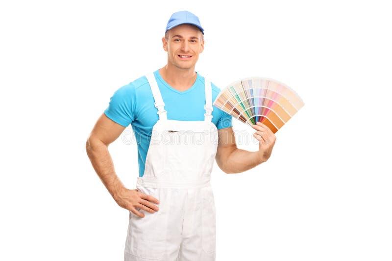 Junger männlicher Dekorateur, der ein Farbmuster hält stockbild