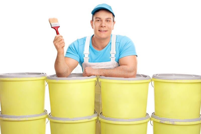 Junger männlicher Dekorateur, der einen Malerpinsel hält lizenzfreie stockfotos