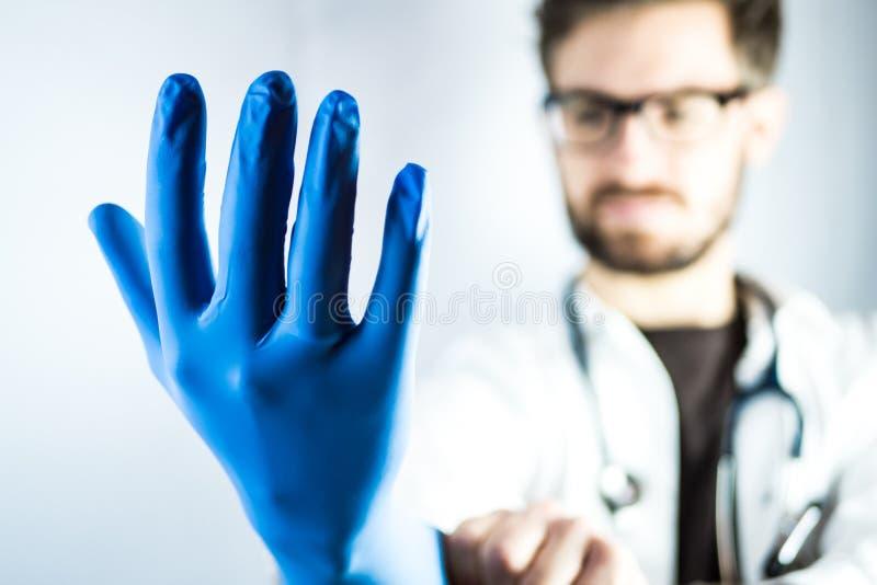 Junger männlicher Doktor, der auf blauen Handschuh sich setzt lizenzfreies stockbild