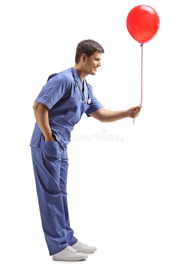 Junger männlicher Doktor in einer blauen Uniform, die einen roten Ballon gibt lizenzfreie stockfotografie