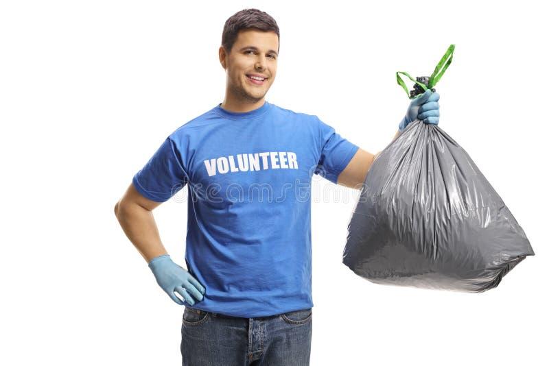 Junger männlicher Freiwilliger, der eine Plastikabfalltasche hält lizenzfreies stockfoto
