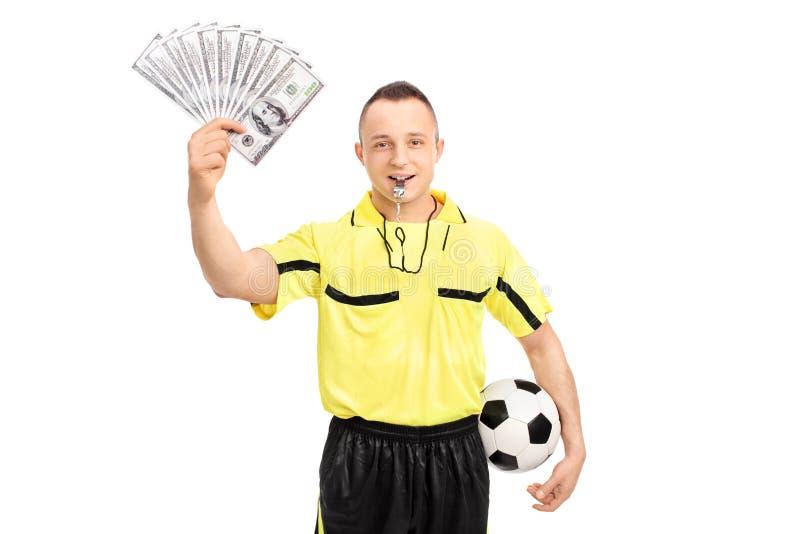 Junger männlicher Fußballschiedsrichter, der einen Stapel Geld hält stockfoto
