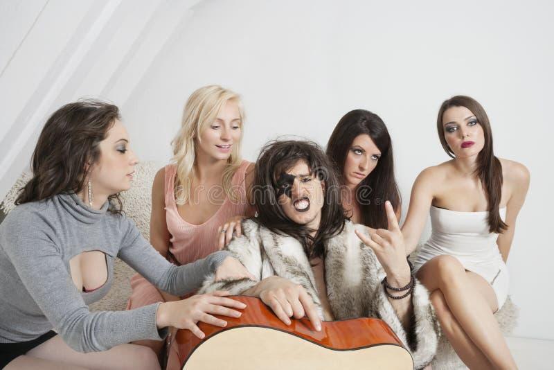 Junger männlicher Gitarrist mit einer kühlen Geste unter weiblicher Gruppe stockbild