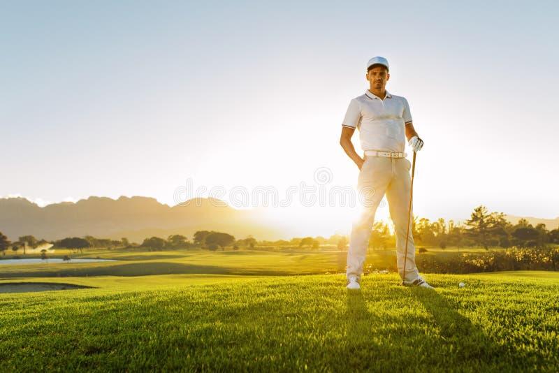 Junger männlicher Golfspieler, der auf Golfplatz an einem Sommertag steht stockbild