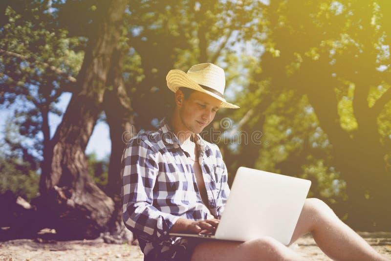 Junger männlicher Grafikdesignerfreiberufler der Reise, der mit lapop auf Strand arbeitet lizenzfreies stockfoto