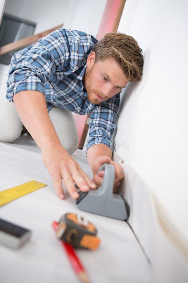 Junger männlicher Heimwerker, der nach Hause Boden an den Kunden installiert stockbild