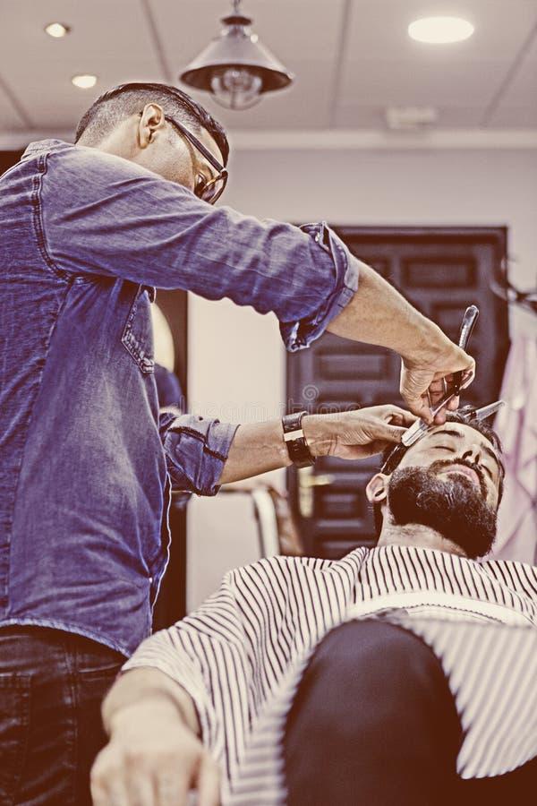 Junger männlicher Herrenfriseur auf einem Bart, der Sitzung rasiert lizenzfreie stockfotos