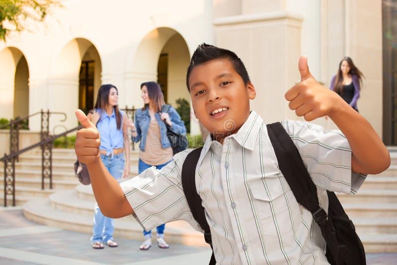 Junger männlicher hispanischer Student Boy mit den Daumen oben auf dem Campus lizenzfreie stockfotografie