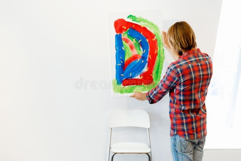Junger männlicher Künstler, der mit einem Bild steht stockfotos