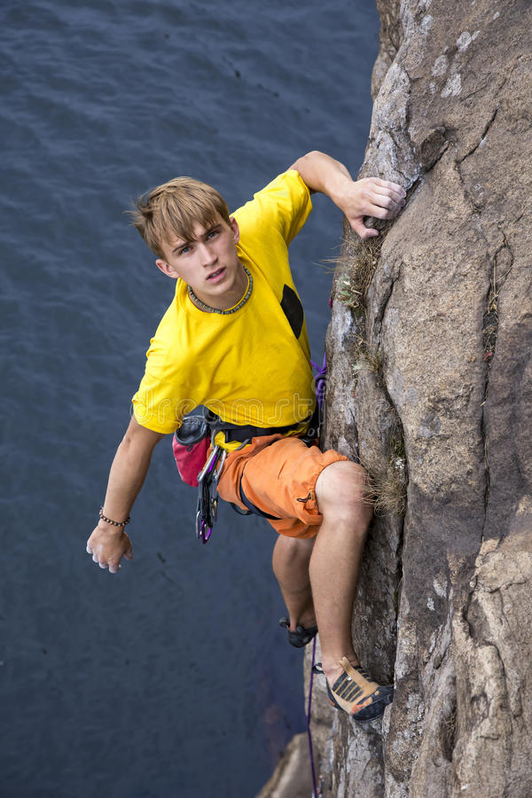 Junger männlicher Kletterer, der über dem Wasser hängt lizenzfreie stockbilder