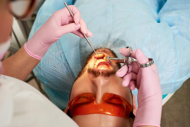 Junger männlicher Kunde mit orange Gläsern lässt Zahneinspritzung von einem Zahnarzt durchführen in den rosa Handschuhen lizenzfreie stockfotografie